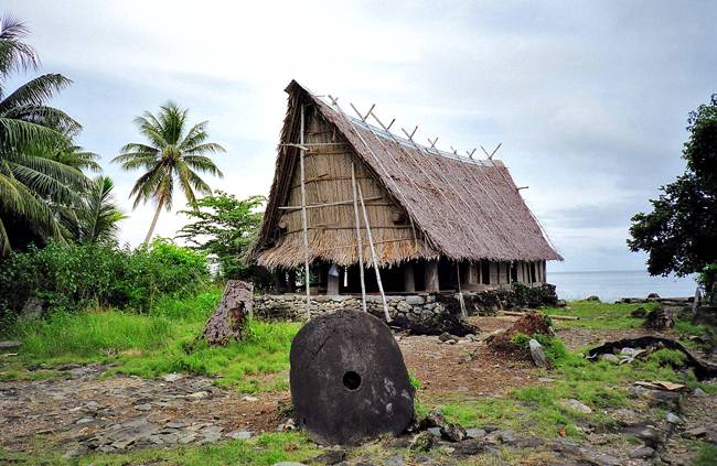 Una piedra Rai frente a una casa de la isla de Yap. ¿Esperando al lechero?
