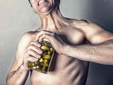 Hombre intentando abrir un frasco hermético
