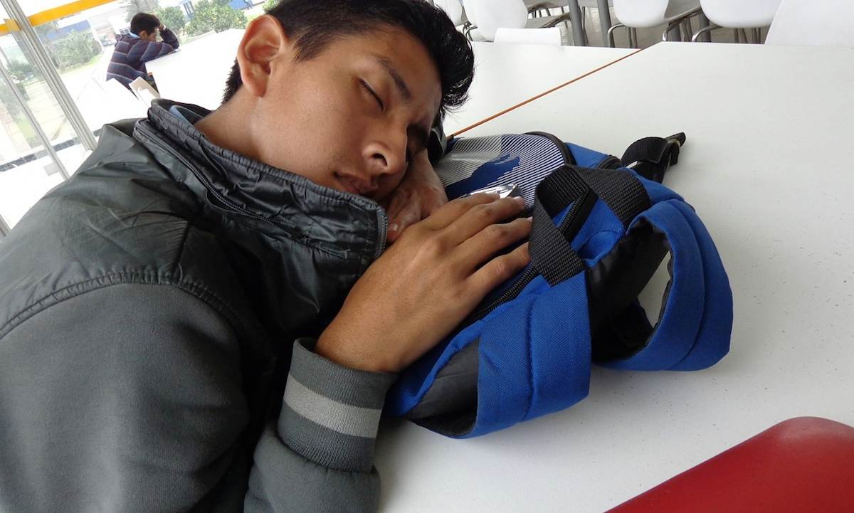 hombre durmiendo sobre su mochila